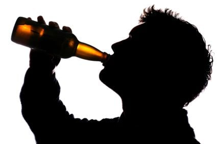 Man drinking bottle of cider silhouette