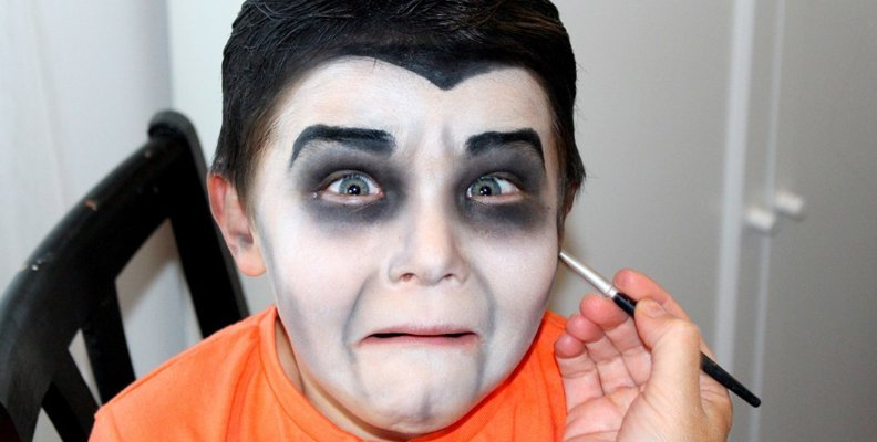 Gör ansiktsmålning på barnen under Halloweenkalaset